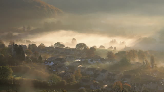 vídeos y material grabado en eventos de stock de early morning autumn mist and chimney smoke from the village of uley, gloucestershire, uk - cotswolds