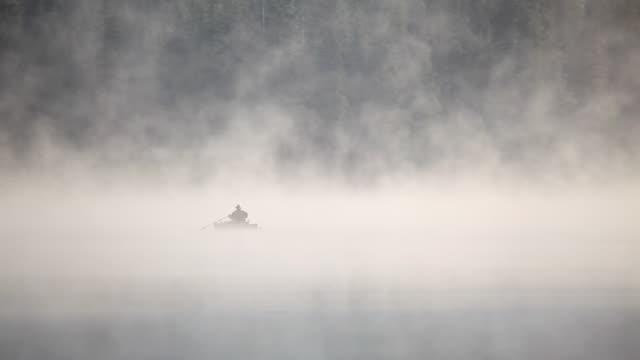 HD early morning fishing on lake in fog