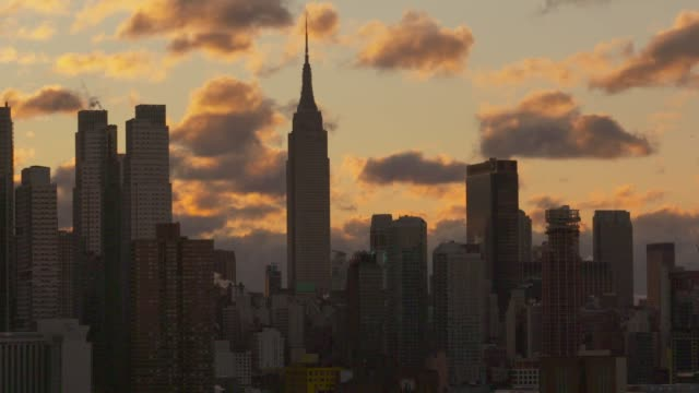 Early morning illuminated clouds move slowly behind the Empire State Building and other New York City skyscrapers.