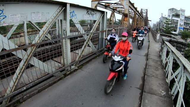 early morning motorbike commuters crossing long bien bridge - bridge built structure stock videos & royalty-free footage