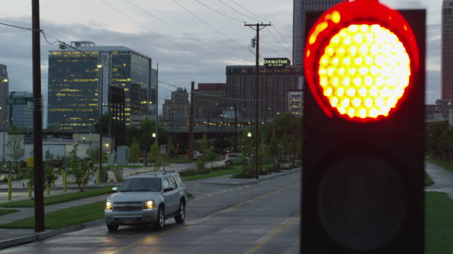 Early morning on an urban street - stop light flashes yellow, then red as an SUV stops at the intersection.