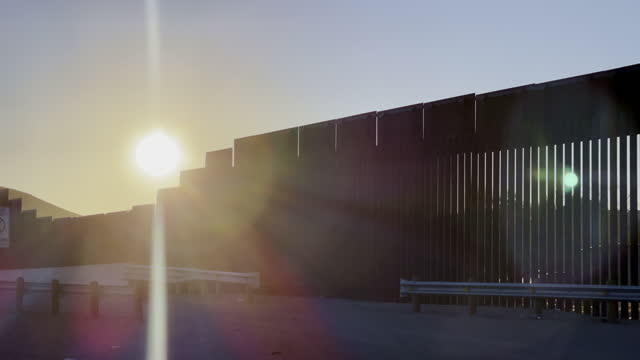 vídeos de stock e filmes b-roll de early morning pan international border wall  with lens flares from sunland park new mexico looking in to puerto anapra chihuahua - vedação
