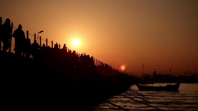 early morning sun rises in sky as silhouetted devotees slowly cross pontoon bridge, metallic looking river streams below them.  kumbh mela, india - pontoon bridge stock videos and b-roll footage