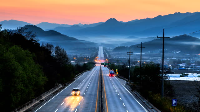 early morning sunrise and clouds over a road near the mountains in gyeonggi-do - traffic time lapse stock videos & royalty-free footage