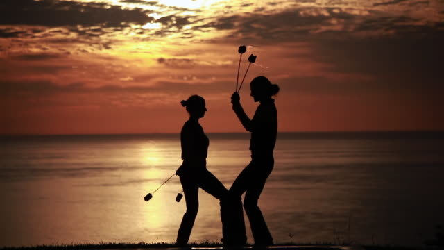 ms early morning sunrise with silhouetted couple performing poi dance with fireballs  / montezuma, costa rica - kelly mason videos stock videos & royalty-free footage