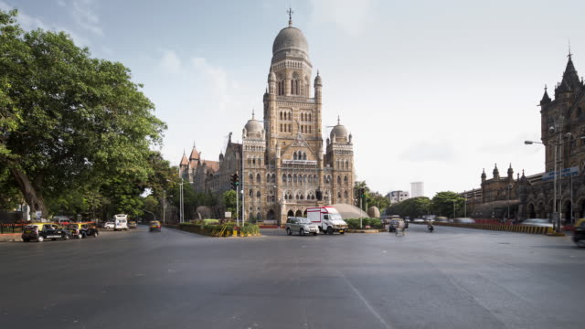 vídeos de stock, filmes e b-roll de tl, ws early morning traffic passes the municipal corporation of greater mumbai / mumbai, india - time lapse de trânsito