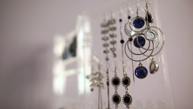 earrings hanging on the stand in in jewelry store - orecchini video stock e b–roll