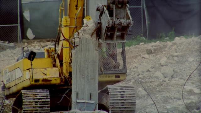 cu, earth mover breaking down concrete column  - veicolo per costruzioni video stock e b–roll