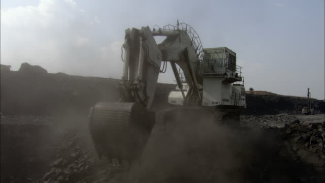 stockvideo's en b-roll-footage met la ws pan earth mover digging coal from pile and releasing coal into another pile / india - hoop samenstelling