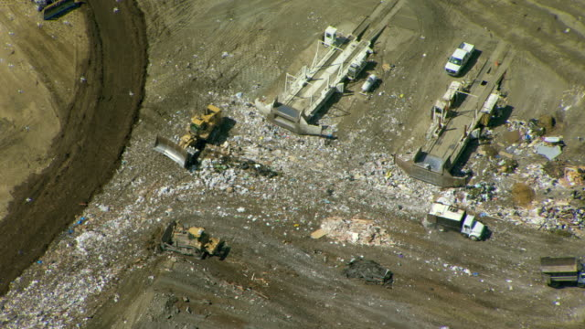 Earth movers push waste and cover it with dirt at the Ox Mountain Sanitary Landfill in San Mateo County, California.