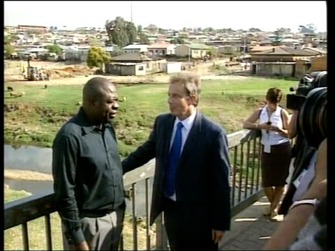 Earth summit Mugabe slams Blair ITN SOUTH AFRICA Johannesburg EXT MS Prime Minister Tony Blair MP along with man on tour of Alexandra township PAN...