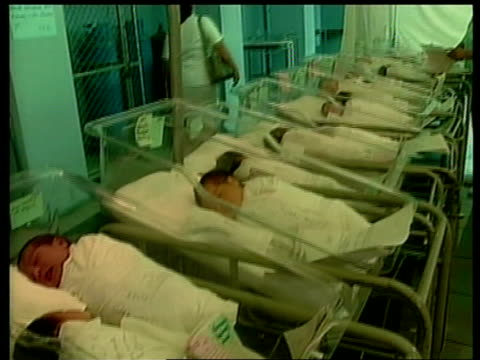 Earthquake aftermath INT Baby orphans lying in cots in makeshift shelter MS Baby in cot