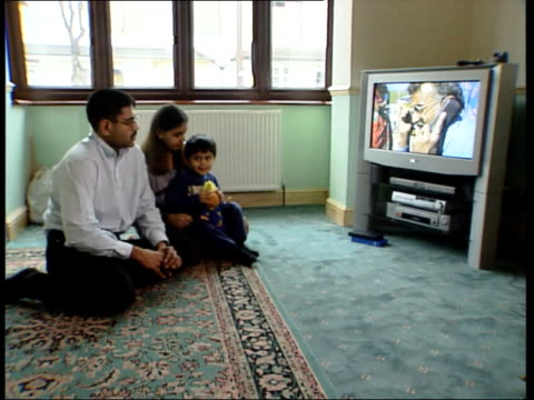 aftermath/aid appeal; earthquake: aftermath/aid appeal; england: london: int family of gurpal naran sitting in living room watching television... - bericht film und fernsehen stock-videos und b-roll-filmmaterial
