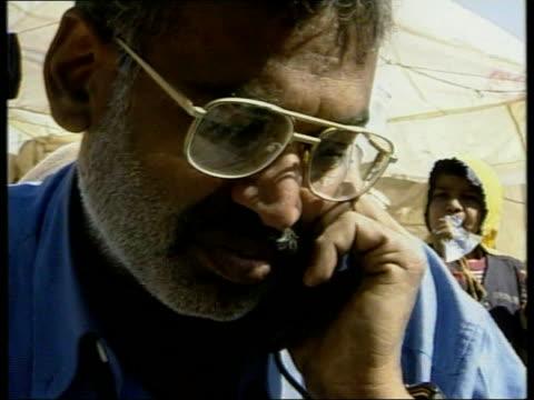 aftermath/aid appeal earthquake aftermath/aid appeal western gujarat ms gurpal naran being handed satellite phone by robert moore naran speaking on... - グジャラート州点の映像素材/bロール