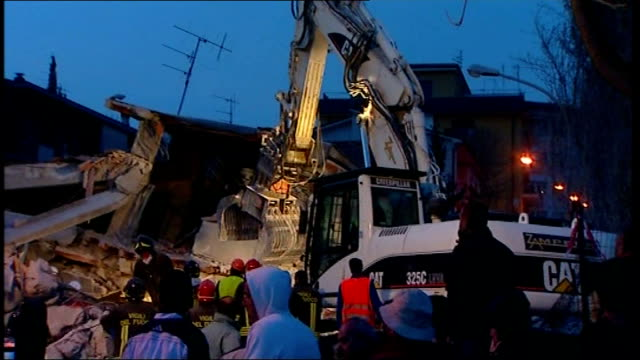 vidéos et rushes de earthquake aftershock / rescue efforts digger removing rubble rescue workers carrying survivor on stretcher and mangled remains of earthquake struck... - démoli
