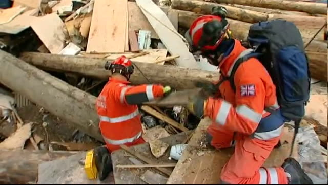 british rescue teams in ofunato japan ofunato int members of uk international search and rescue team searching through debris and furniture in room... - ダメージ点の映像素材/bロール