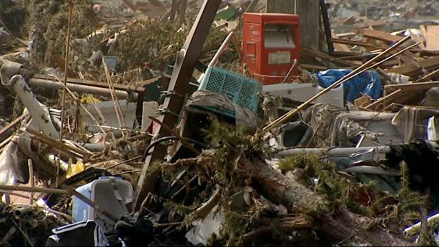 general views of damage to rikuzentakata japan rikuzentakata ext debris poking through smashed windows pull back debris / building surrounded by... - toccare con un dito video stock e b–roll
