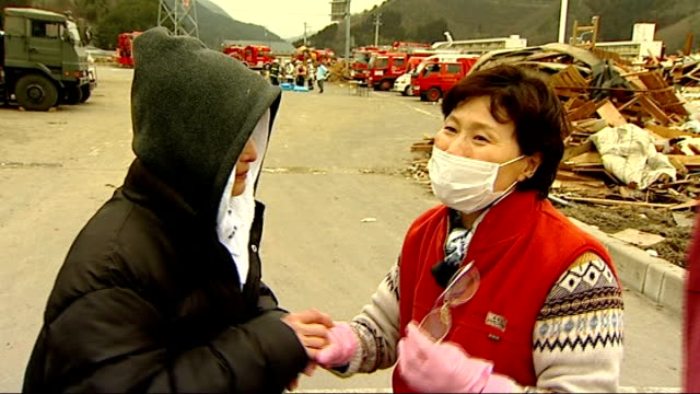 general views of otsuchi rescue teams / people searching ruins / interviews with survivors / body bags women hugging each other / interview women sot... - 地震点の映像素材/bロール