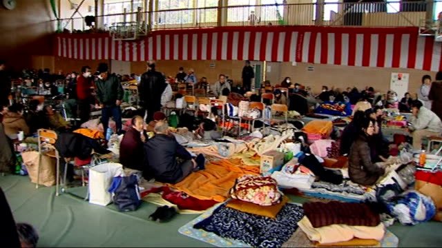minami sanriku and rikuzentakata survivors at rescue centre / interviews with survivors gvs men women and children seated and lying on floor in... - evacuazione video stock e b–roll