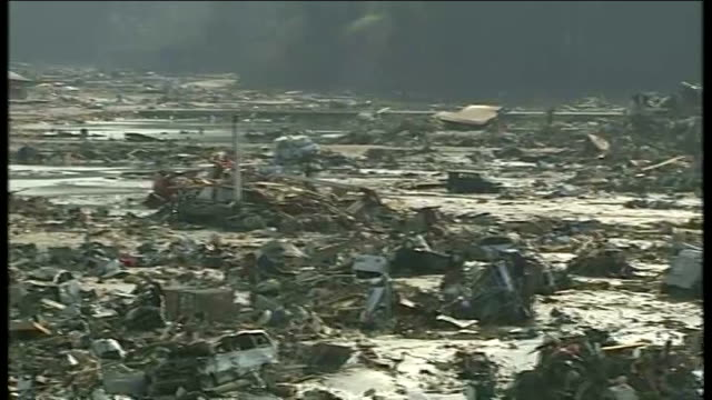 earthquake and tsunami aftermath: more than 10,000 feared dead / rescue efforts; japan: minamisanriku: ext destroyed buildings and debris pull out... - tsunami stock videos & royalty-free footage