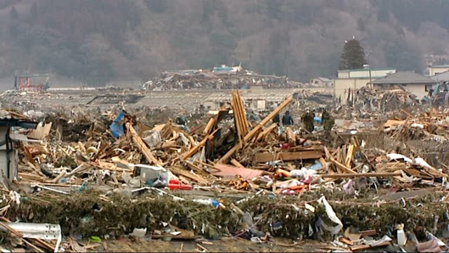 Scenes of devastation in Otsuchi People searching / Rescue workers army and emergency services / Forest fires Car at angle on debris near railings /...