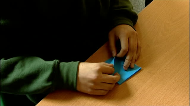 vídeos de stock e filmes b-roll de earthquake and tsunami: richmond schoolchidren make paper cranes to raise money; england: london: richmond: sheen mount school: int speeded up... - origami