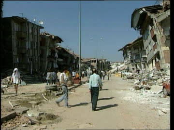 death toll rises; turkey: adapazari: ext gv row of buildings partly demolished by earthquake to more on opposite side of road overturned car amidst... - moving up点の映像素材/bロール