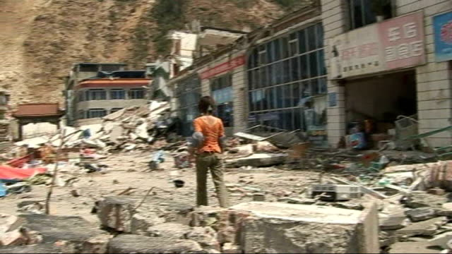 focus changing from rescue to recovery beichuan ext school clock lying on ground pan to wreckage back view lone person walking through rubble in... - 四川省点の映像素材/bロール