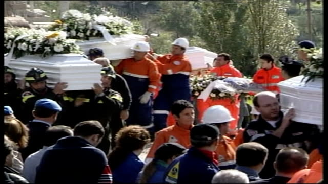 vidéos et rushes de funeral for victims; day tgv coffins of victims carried along thru crowds gathered for funeral ditto i/c family members along coffins carried along... - victime