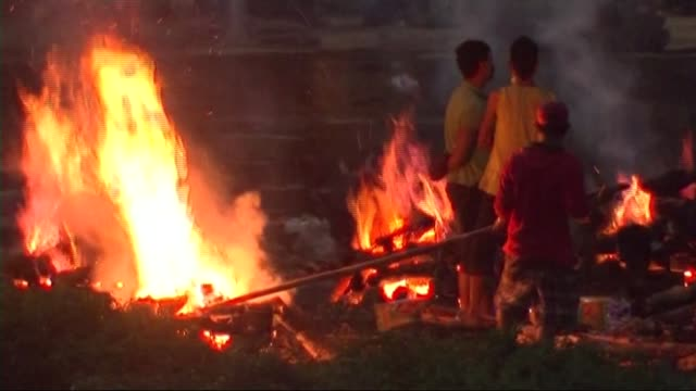 funeral pyres of earthquake victims burning; nepal: ext / dusk man standing with mask on chin and hand on heart as praying / traffic along road /... - hand on heart stock videos & royalty-free footage