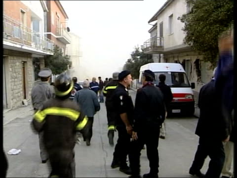 vídeos de stock e filmes b-roll de school death toll rises; en: juliet bremner itn italy: san giuliano di puglia: ext people along in town after further earth tremors part of building... - shaking