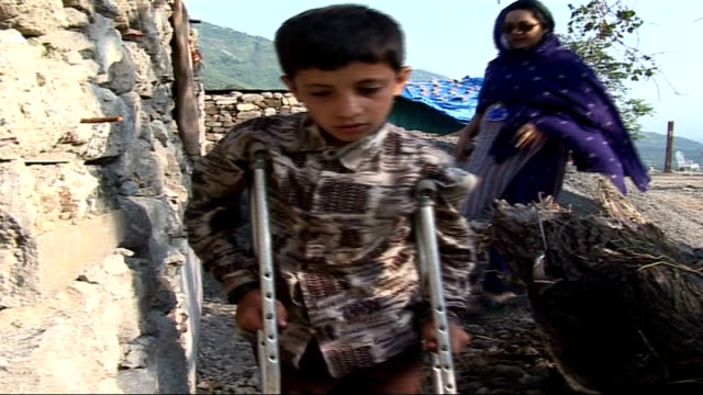 Earthquake survivors still at risk in camps one year later Maseen towards with crutches followed by female interpreter Maseen along among earthquake...
