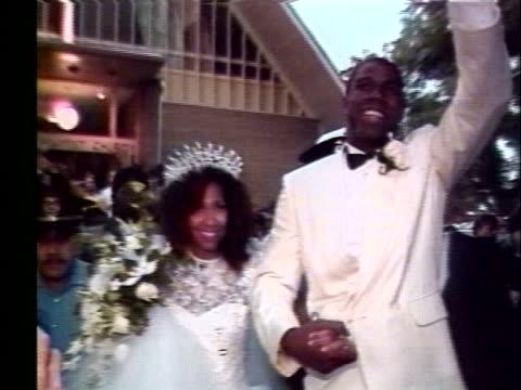 "earvin ""magic"" johnson, jr., and his wife, earlitha, emerge from a church after their wedding. - マジック・ジョンソン点の映像素材/bロール"