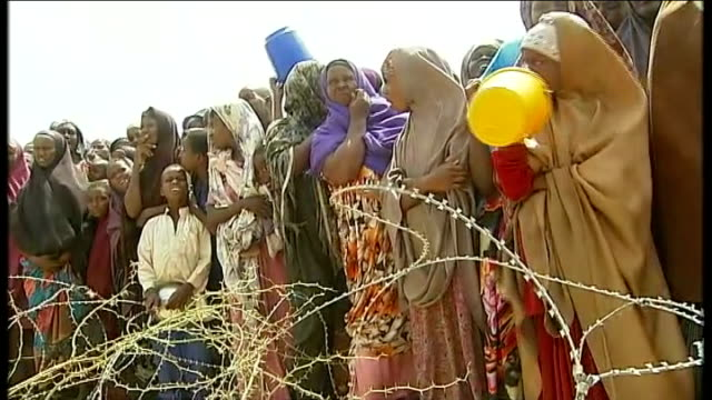 AlShabaab maintains ban on western aid agencies Group of women refugees queue behind barbed wire fencing for food