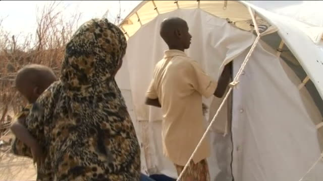 vídeos de stock e filmes b-roll de further arrivals at dadaab refugee camp; ext mohamed seated talking with reporter mohamed entering tent with his foster mother group of refugees... - acolhimento familiar