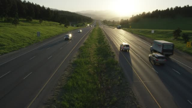 east and westbound highway traffic along interstate-70 in the rocky mountains of colorado at sunset - road trip stock videos & royalty-free footage