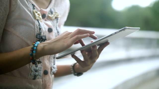 vidéos et rushes de east asian culture: femme asiatique à l'aide de tablette numérique dans jardin - parc naturel
