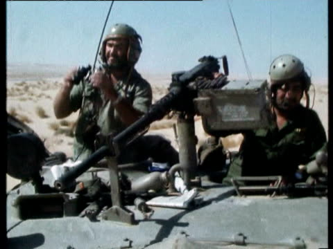 vídeos de stock, filmes e b-roll de east bank of the suez canal, israeli sherman tanks cross desert, tank commander and machine gunner , machine gunner as tank passes wreck, troops... - 1973