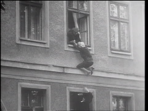 vídeos de stock e filmes b-roll de east berlin guards try to pull woman into window as west berliners pull her to ground - 1961