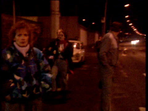 stockvideo's en b-roll-footage met oberbaum bridge ext / night side view of east german youths in trabant car along through border crossing point people queuing at customs post woman... - 1989
