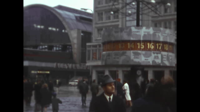 East Berlin train station Alexanderplatz with arriving urban railway big clock Urania Weltzeituhr with different times of the world / panning to the...