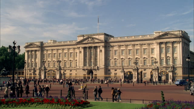 ws east front of buckingham palace with pedestrians / london, england, united kingdom - バッキンガム宮殿点の映像素材/bロール