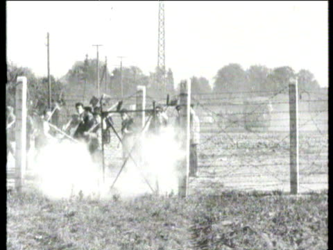 the wall along border is now a double line of high concrete posts and barbed wire with a ditch behind line of east german workers led by flag bearer... - 1961 stock-videos und b-roll-filmmaterial