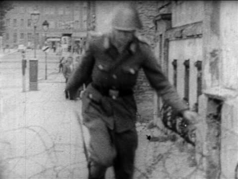 vídeos de stock e filmes b-roll de east german guard jumps over barbed wire drops gun runs to truck / escaping east berlin - 1961