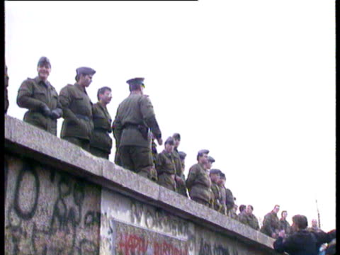vídeos de stock e filmes b-roll de east german guards on top of wall west germans beginning to pull down sections of the wall are sprayed by eastern water cannon fall of the berlin... - muro circundante