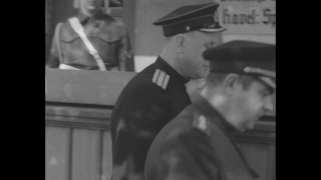 east german officer leaves a building under guard with two sentries / the tail end of a sedan driving away - kalter krieg stock-videos und b-roll-filmmaterial