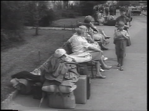 vídeos de stock, filmes e b-roll de east german refugees sitting on bench outdoors / beginning of berlin wall / west germany - fronteira internacional