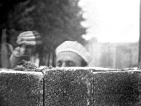 east german soldiers watch workers lay bricks onto the partly constructed berlin wall august 1961 - 1961 stock-videos und b-roll-filmmaterial