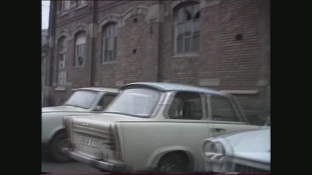 east germany general views; east germany: leipzig: children running around in park pull out to flats: track lr factory; man seen through fence... - east germany stock videos & royalty-free footage