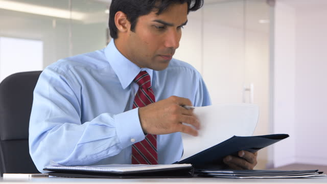east indian businessman taking notes - one mid adult man only stock videos & royalty-free footage